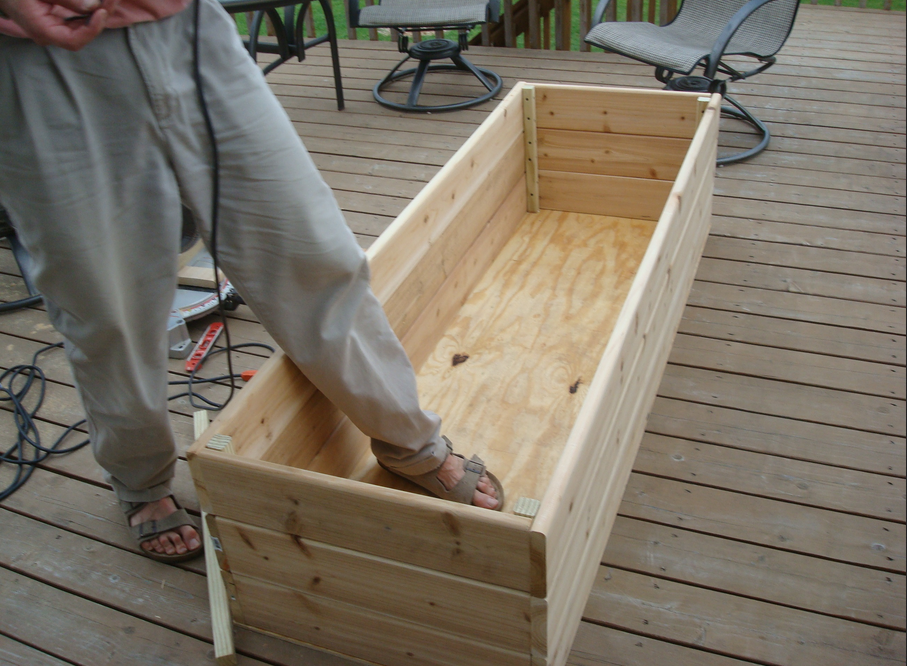 man's foot in garden box