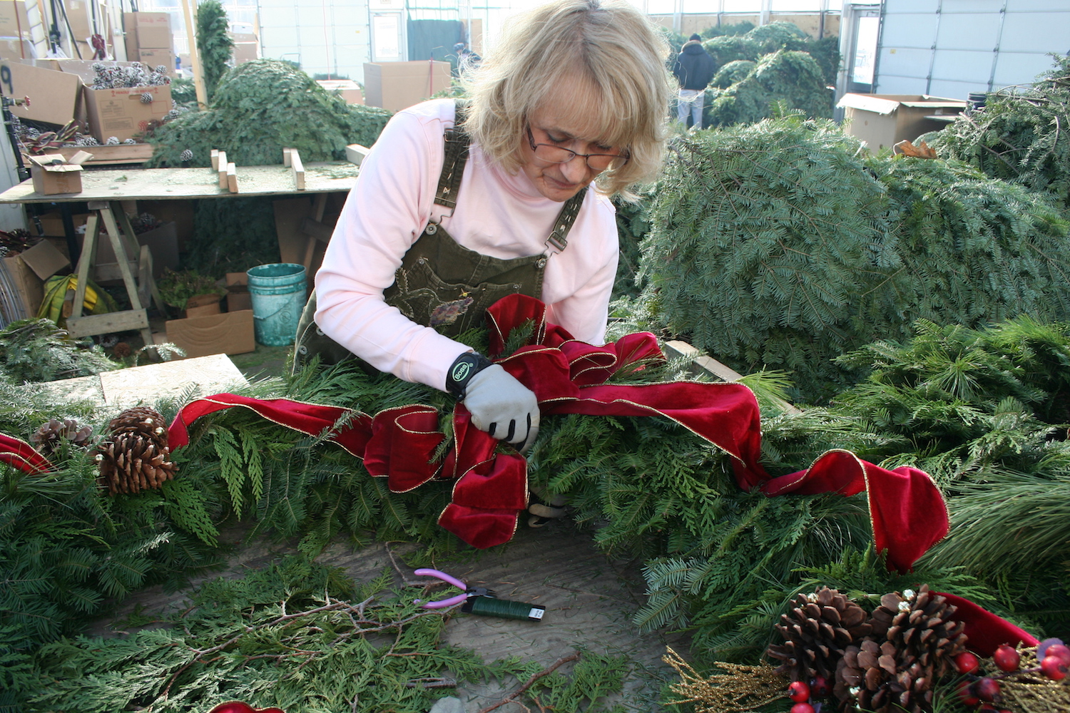 woman working on large wreath