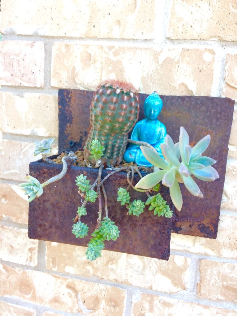 budha and succulents decorating a garage