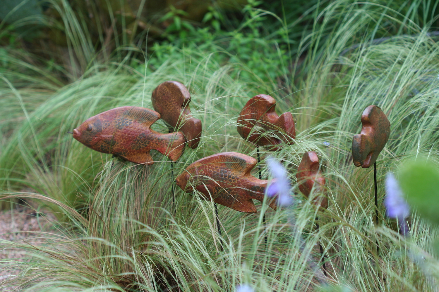 wooden fish swimming through grass
